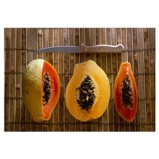 Sliced papayas and knife on a reed mat Poster