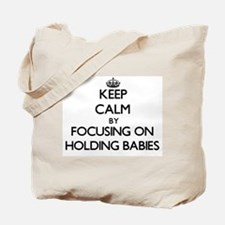 Keep Calm by focusing on Holding Babies Tote Bag