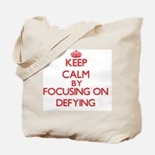 Keep Calm by focusing on Defying Tote Bag