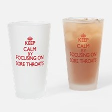 Keep Calm by focusing on Sore Throa Drinking Glass