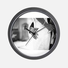 Groom holding bottom of bride black and Wall Clock
