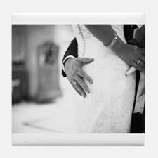 Groom holding bottom of bride black a Tile Coaster