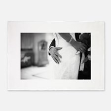 Groom holding bottom of bride black 5'x7'Area Rug