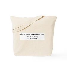 Buy us a shot, she's tying th Tote Bag