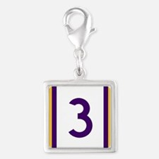 three purple and gold Charms