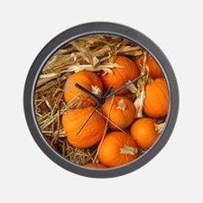 a bunch of small pumpkins on hay Wall Clock
