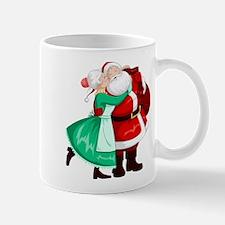 Mrs Claus Kisses Santa On Cheek And Hugs Mugs