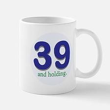 39 and holding Mugs