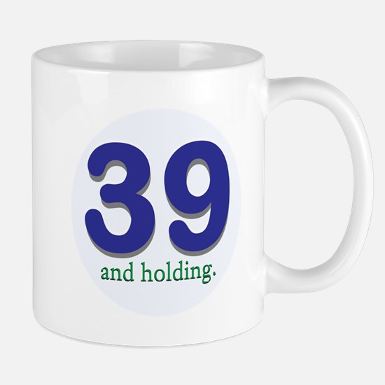 39 and holding Mugs