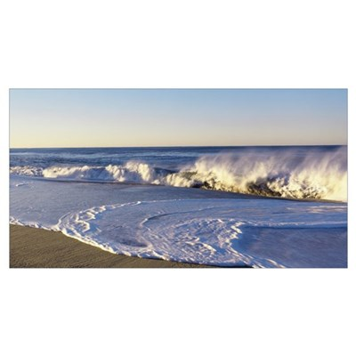 View of waves washing up on a beach Poster