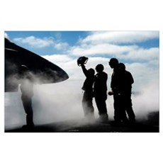 A flight deck crew member shows the pilot of an F/ Poster