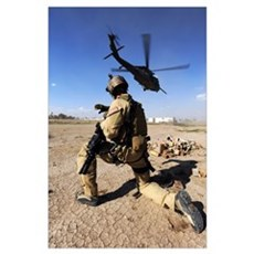 A soldier conducts security for an HH60 Pavehawk h Poster