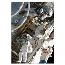 Astronauts participate in extravehicular activity Framed Print