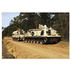 An M88 recovery vehicle begins to tow an M992 fiel Canvas Art