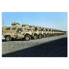 Mine Resistant Ambush Protected vehicles sit at Ca Framed Print