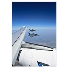 Two F16 jet fighters fly alongside the wing of an  Framed Print