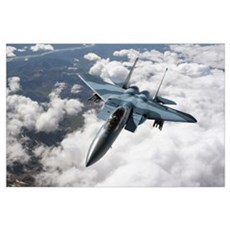 An F15C Aggressor flies over a mountain range Poster