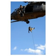 A pararescueman rappels from an HH60 Pavehawk heli Poster