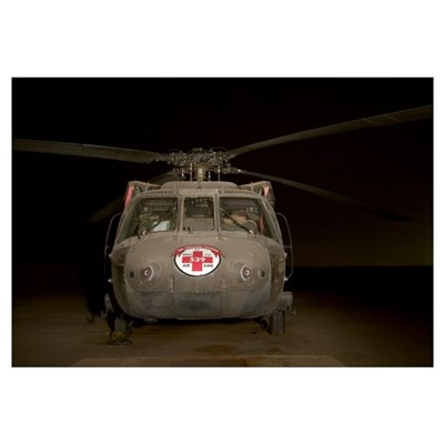 A UH60 Blackhawk Medivac helicopter sits on the fl Framed Print