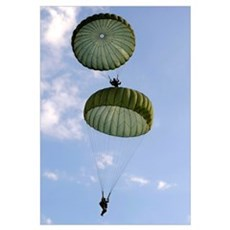 U.S. Army Soldiers parachute down after jumping fr Framed Print