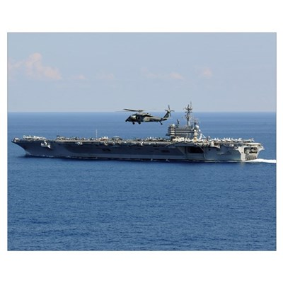 An MH 60S Seahawk helicopter flies over USS George Poster