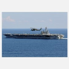An MH 60S Seahawk helicopter flies over USS George
