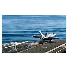 An F/A 18E Super Hornet launches from the flight d Poster
