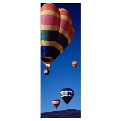 Low angle view of hot air balloons flying in the s Poster