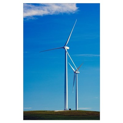 Pair of wind farm turbines in green grass, blue sk Poster