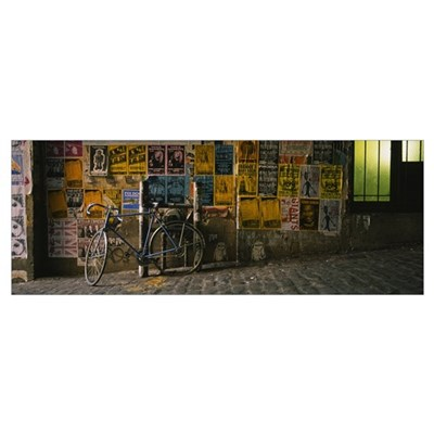 Bicycle leaning against a wall with posters in an Poster