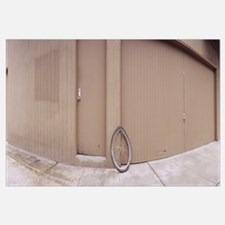 Bent bicycle tire leaning against a wall near a cl