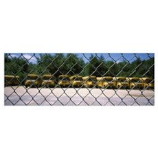 Chain-link fence with school buses in the backgrou Framed Print