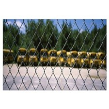 Chain-link fence with school buses in the backgrou