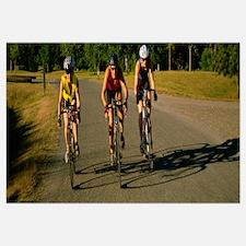 Three mid adult women cycling