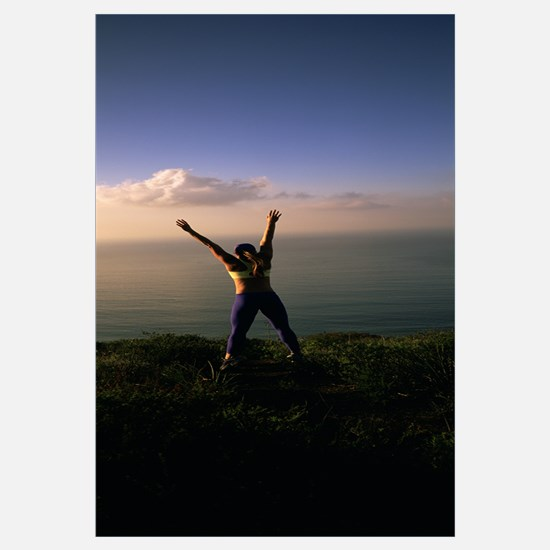 Rear view of a young woman exercising on a hill