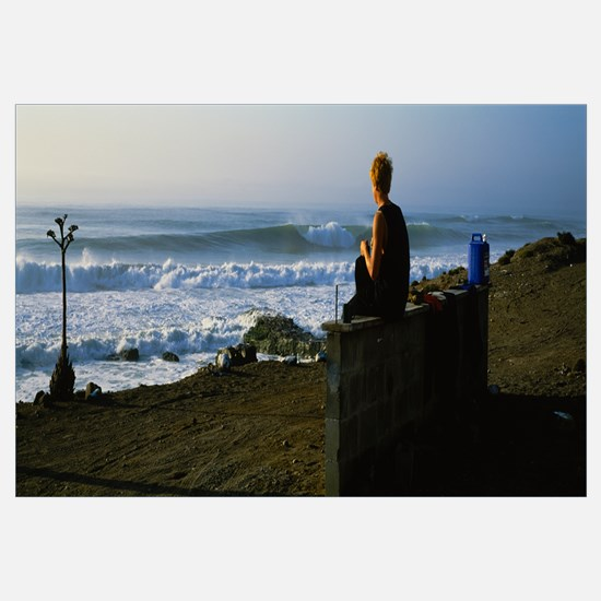 Rear view of a woman sitting on a stone wall on th