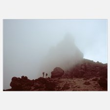 Lava tower in heavy fog, silhouetted hikers, Mount