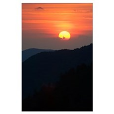 Sun setting behind clouds, silhouetted mountains,  Poster