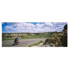 Rear view of a man cycling on a road, Badlands, Th Canvas Art