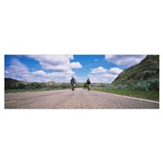 Rear view of two people cycling on a road, Badland Poster