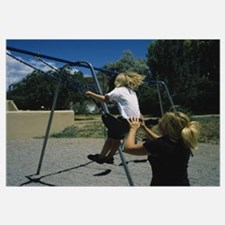 Rear view of a mother pushing her son on a swing,