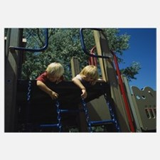 Low angle view of two boys playing on the jungle g