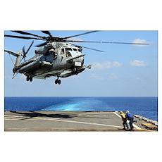 A CH-53E Super Stallion lifts off from an amphibio Poster