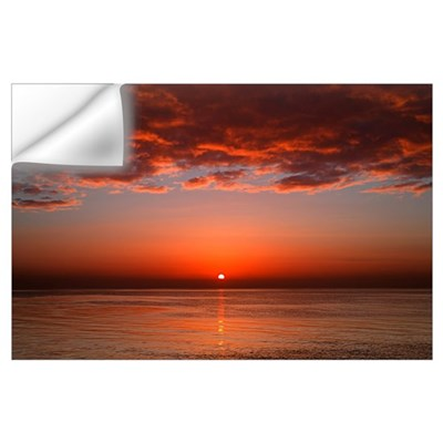 A layer of clouds is lit by the rising sun over Ri Wall Decal