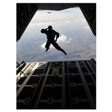 A paratrooper salutes as he jumps out of a C-130J  Poster