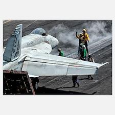 Flight deck crew position an F/A-18E Super Hornet