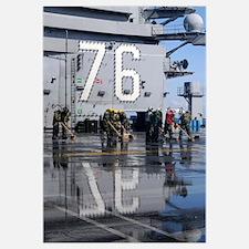 Sailors scrub the flight deck aboard the aircraft
