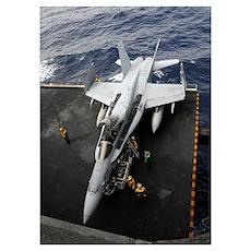 Sailors move an F/A-18C Hornet into the hangar bay Poster