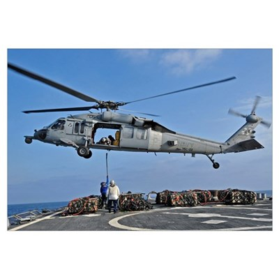 Sailors attach a cargo pennant to a MH-60S Sea Haw Canvas Art