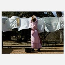 Rear view of a woman drying clothes on a clothesli